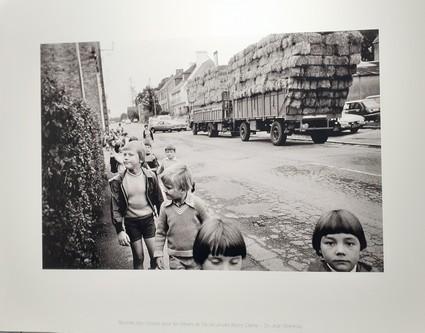 A Saint Jean Brévelay, sortie d'école et traversée du bourg par de grandes remorques de bottes de paille.
