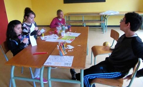 Quatre jeunes lors d'un atelier réalisent dessins et découpage